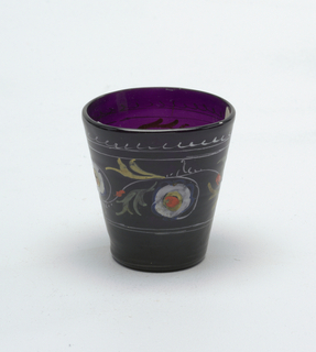 Purple glass beaker with painted decoration of white flowers