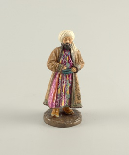 Man dressed in Turkish costume with turban, standing with hands at belt, richly patterned polychrome robe and coat.