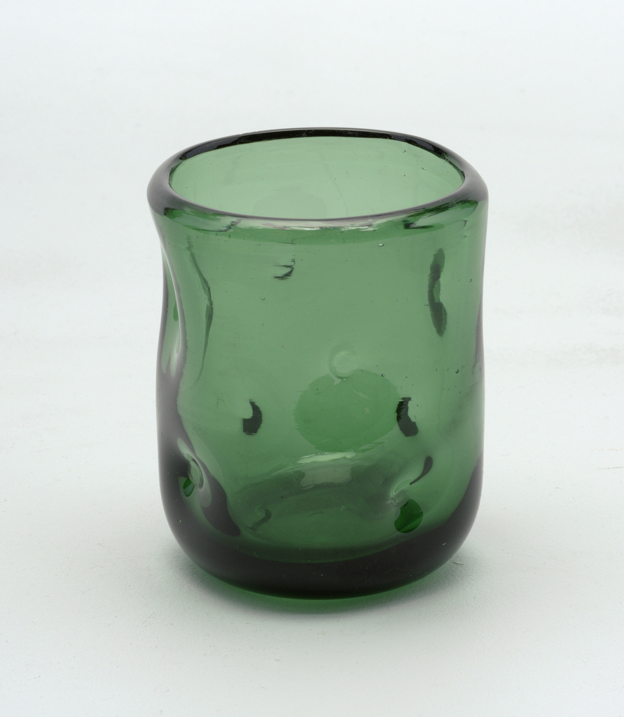 Thick, transparent green cylindrical form with dimpled surface.