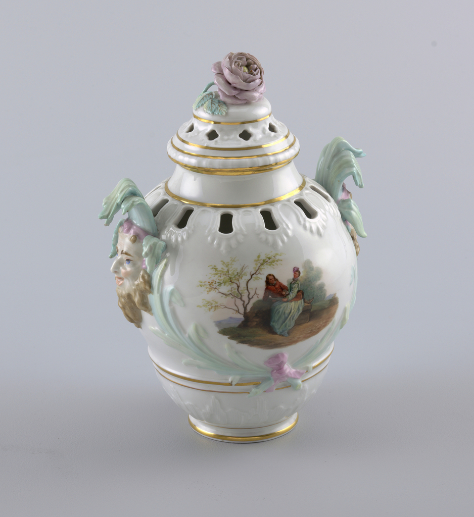 Potpourri vase molded with relief decoration around piercings on shoulder and lid. Gilded bands at base, neck and lid. Handles with mascarpone crowned with water reeds. Painted courtship scenes. Knob in the form of a rose.