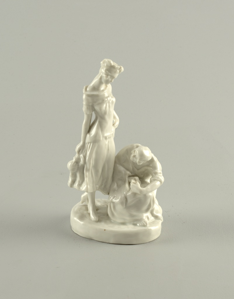 Two figures: a young woman in stylish outfit standing, looks down at seated older woman in peasant garb; circular base; unpainted.