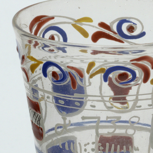 Clear glass goblet with 2 rows of shields decoration painted on body.