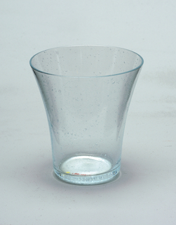 Cylindrical body of transparent bluish bubbly glass flares outward to a slightly thickened lip.