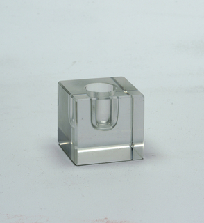Cube-shaped, chamfered at all edges. Solid, except for cylindrical hole for candle, more than one half of cube, and with spherical bottom.