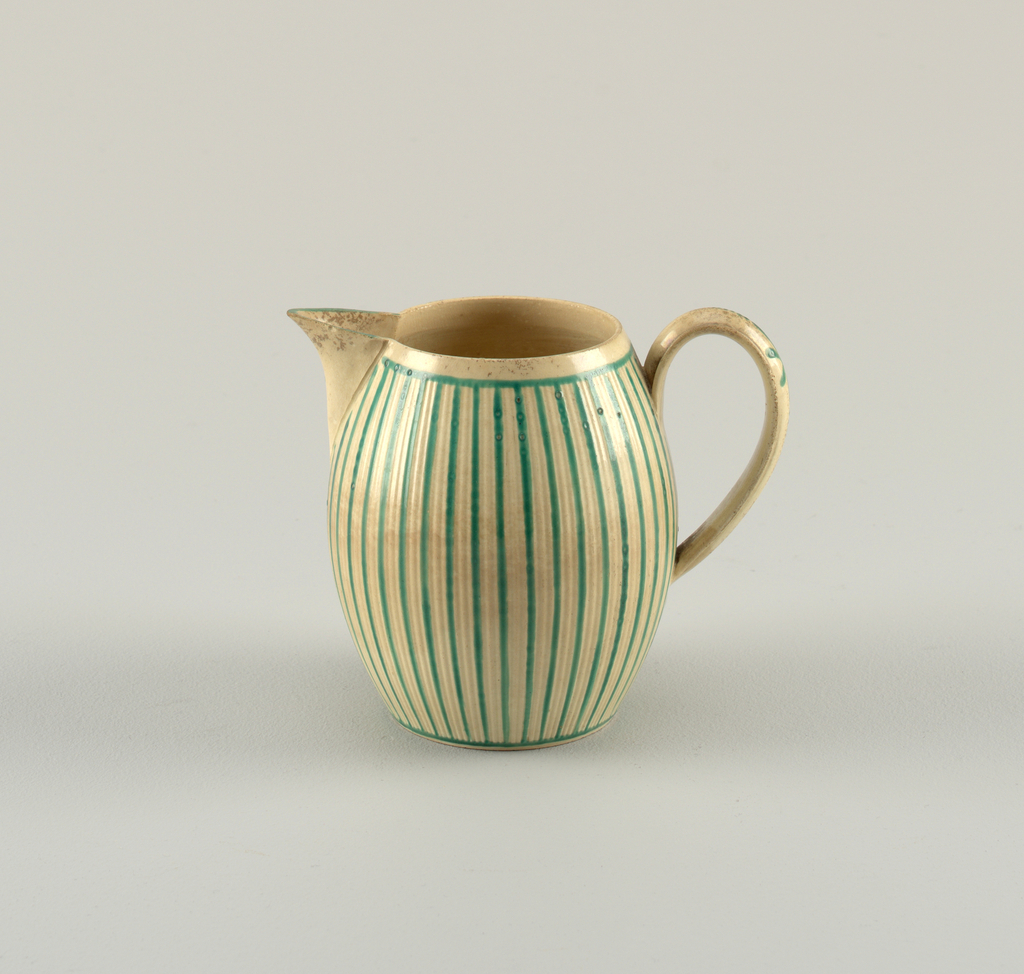 Barrel-shaped body with pointed spout, ribbed strap handle. Body ribbed, and stiped in green.