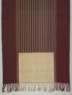Ulos ragidup, 'the cloth with the pattern of life', is a large ceremonial selendang (shoulder cloth) which is wrapped around the groom's mother by the bride's father at a wedding. Center area in dark maroon with vertical stripes of light blue and a bright red-brown. Ornamented on either end with intricate insets of cream color with horizontal bands of design, by making use of one additional warp. Wide borders in dark red, with a narrow stripe of dark blue on outer-most side and a stripe showing a geometric pattern in gold on the inner most side (touching the center panel), run the length of the piece on both sides of the center panel. Woven in three sections and fringed.