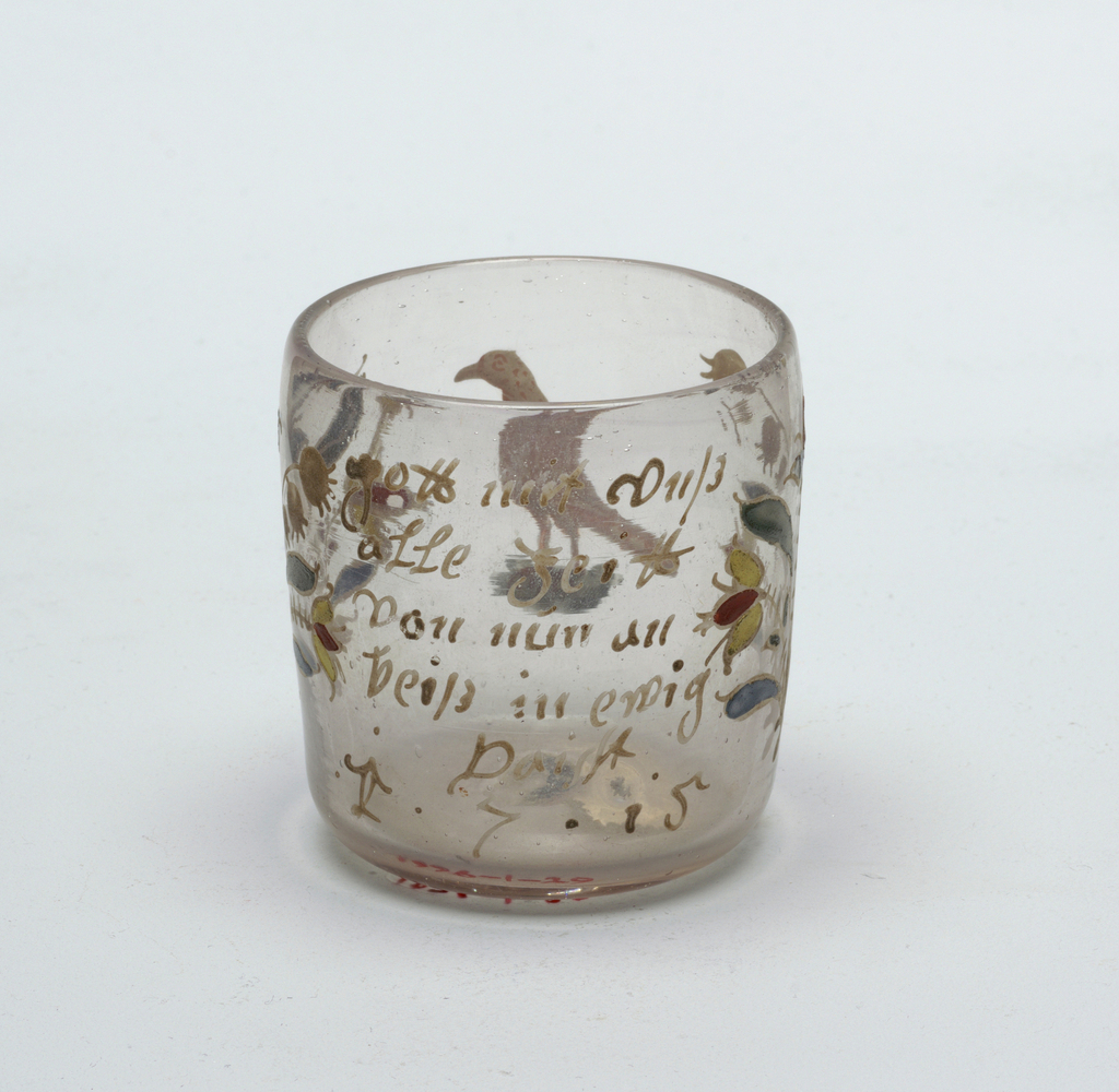 """Clear glass beaker with painted decoration.  Glass has slight rose colored cast.  Body of beaker has slight bow shape.  Sticker """"125"""" on bottom"""