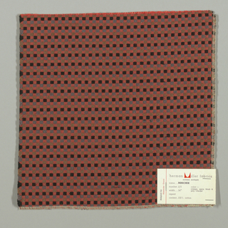 Pattern of small checks in red, grey, dark blue and brown. Warp threads are red and beige and weft threads are black with supplementary weft in grey, dark blue and brown.