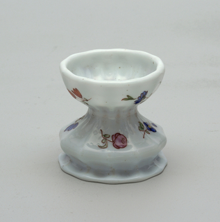 Footed cup in white glass.  Cup and foot has vertical ridges (12).  Painted decoration