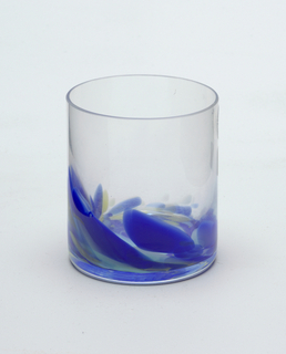 Clear glass tumber with blue, aqua and yellow glass in vertical wave-like pattern at base