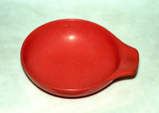 Reddish-orange bowl with outturned handle.