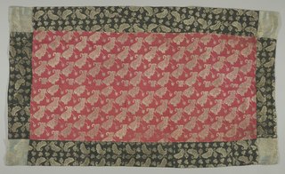 Panel made up of two kinds of silk in the same design. Center section of the panel is red with small indefinable leaf pattern of brocaded metallic thread. Five inch border is blue in the same design. Corners are made of squares of less fine, blue brocaded fabric. One selvage present on the red textile indicates machine manufacture.