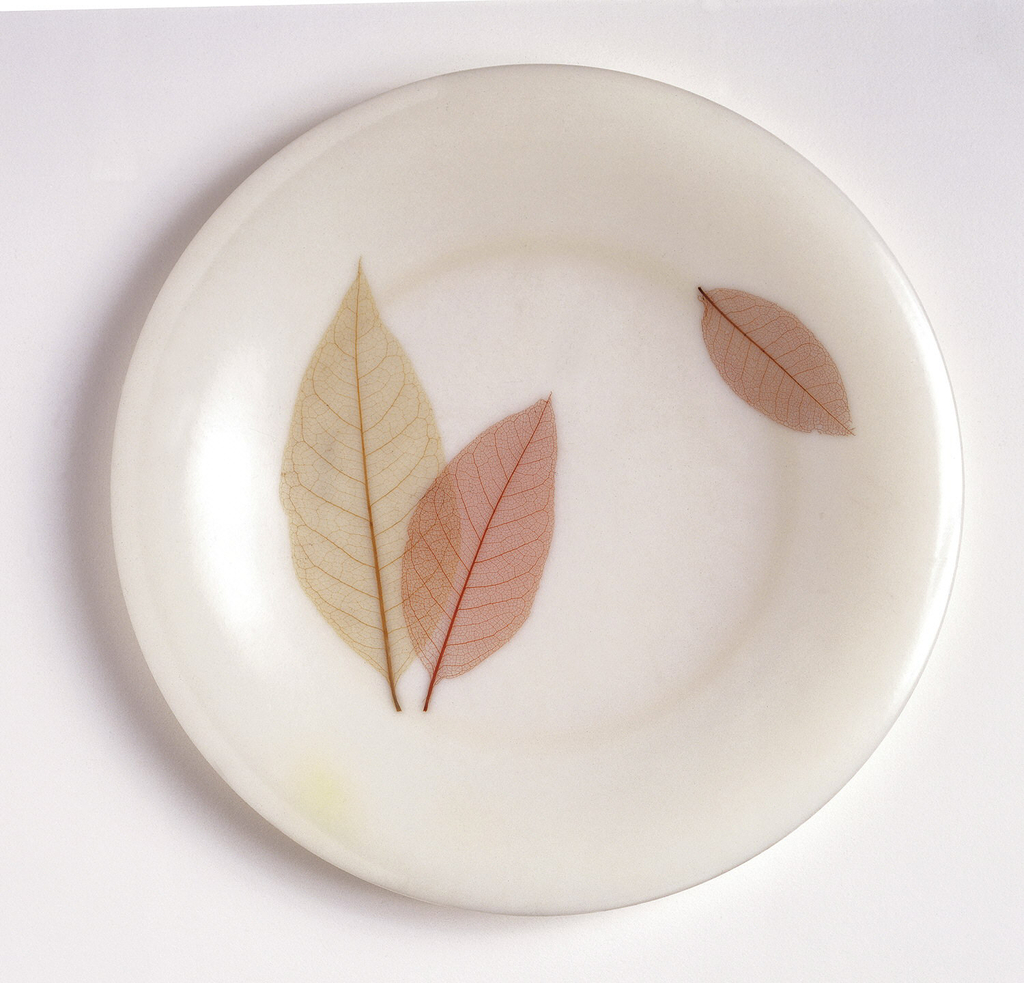 A white plastic dinner plate with two leaves overlapping in the center left and a sideways smaller leaf on the rim of the right side. Leaves are realistic and in natural shades of pink, cream, and brown
