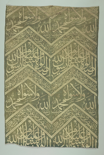 Zig-zag bands with Kufic writing in green and white. Both selvages present.