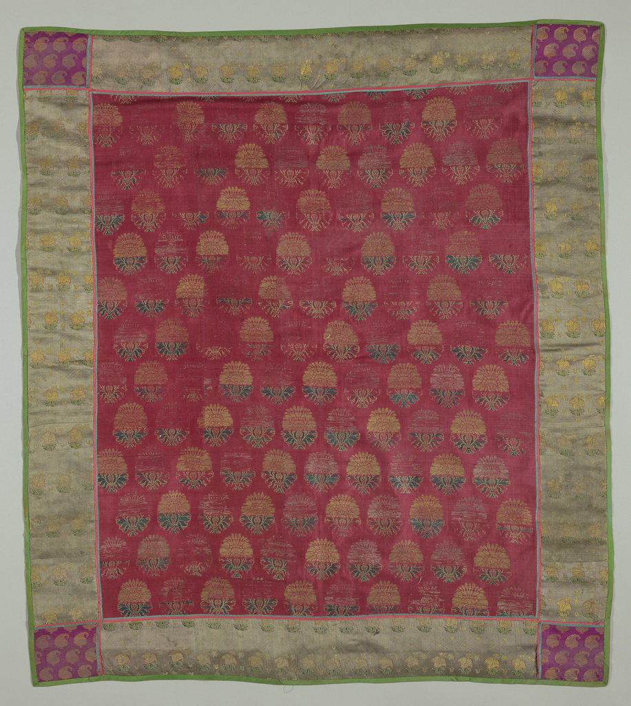 Red plain weave center brocaded in a detached flower design in gold, green, and white silks. Pattern arranged in horizontal rows. Trimmed with a wide band of gray-green silk twill stamped in a diagonal design and brocaded in a small flower pattern in white, rose and green silks. At corners, square insertion of red silk brocaded in small cone design in gold. Trimmed with pink and green piping and lined with pink taffeta.