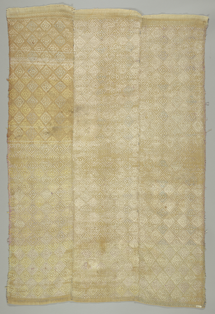 Buff cotton panel with an allover lozenge pattern brocaded in pastel silks. Worn and soiled on the obverse, the colors only appear on the reverse. Made of three narrow lengths sewn together. Yarns are thick.