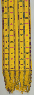 Sash of dark yellow handwoven cotton with stripe of green and dull red brocaded in small block designs in red or in green. Detached geometric patterns in red, pink, green and black between stripes. Long fringe from the warps.