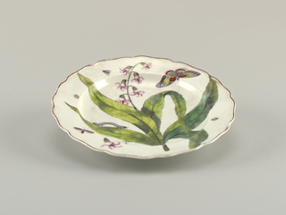 A plate with a wavy, brown-edged rim. Decoration showing flowering plant and insects.