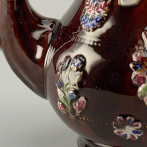 """A brown teapot and dome lid decorated with a flower pattern. On the side, a white arch says: """"I Like it Good"""". The knob on the lid a miniature teapot."""
