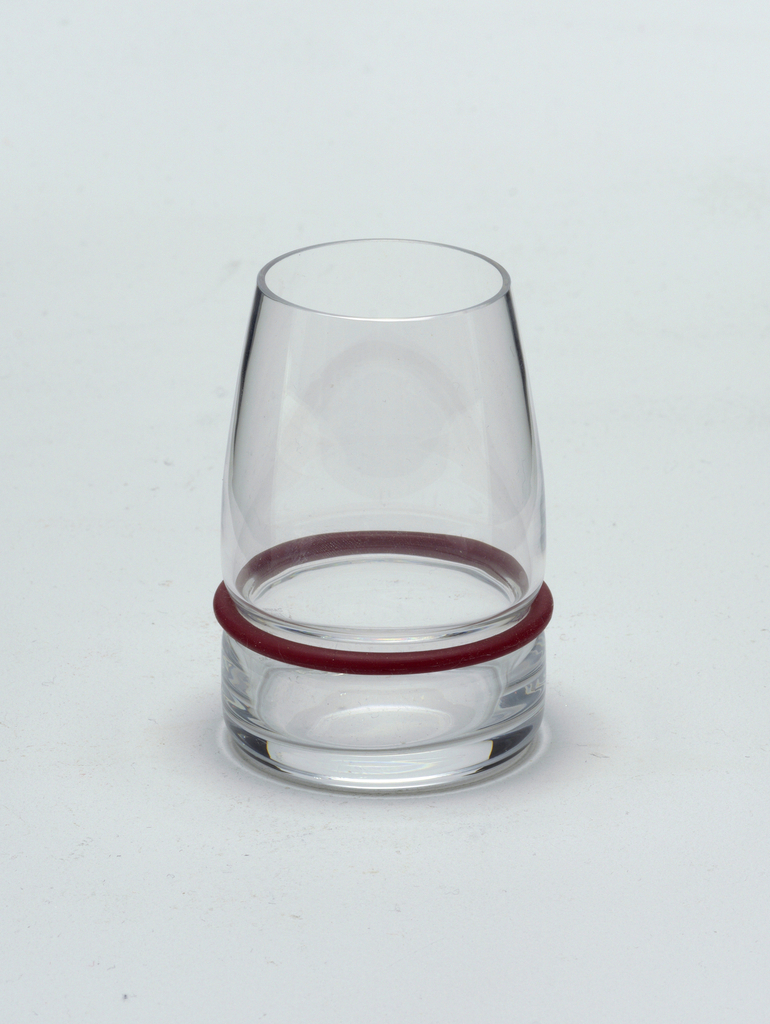 "Clear blown glass. Beaker/liqueur glass. Flat based beaker of cylindrical shape; sides curve inward toward lip. Side waisted above base to hold silicone ""bumper"" ring: set of silicone rings in plum, black, and white supplied with set."