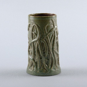 "Tan-colored stoneware body, cast. Tall cylindrical body tapering outward at base. Design of cattails in relief around body. Covered with green matte glaze with ochre effects defining the design, called ""verte antique"" glaze. Bottom glazed the same. Interior covered with terra cotta colored matte glaze."