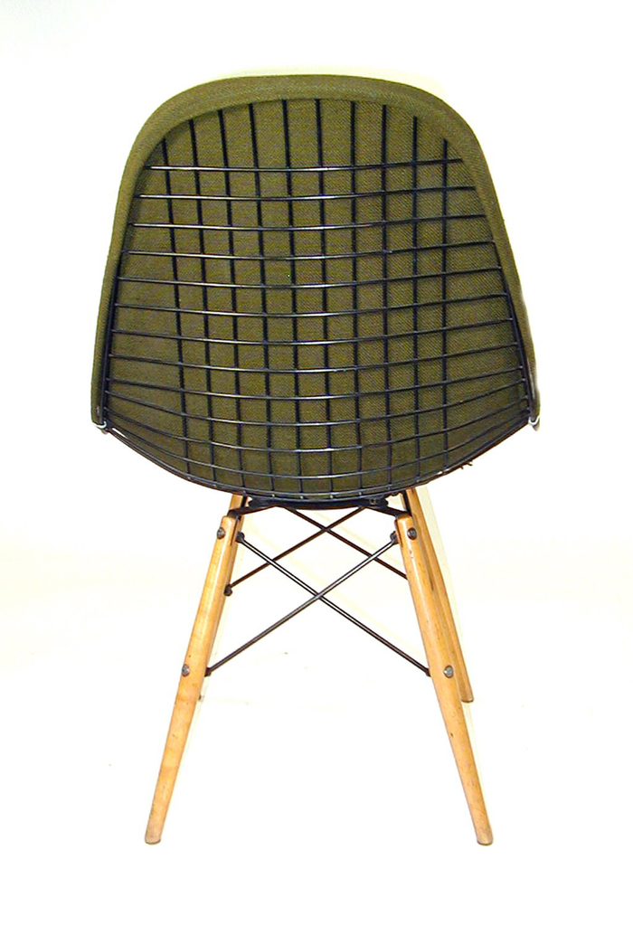 Mesh frame covered with upholstery, soft L-shaped back and seat with metal crisscrossed frame underneath attached to radiating wooden legs.