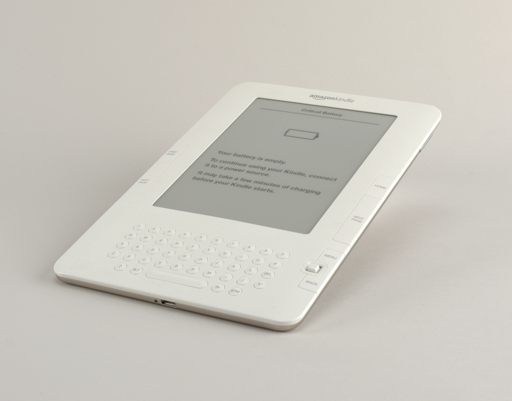 Thin rectangular tablet form of white plastic with large rectangular flat screen set above keyboard composed of small circular keys; large rectangular fuction keys and small directional control flanking either side of screen; aluminum panel on back.