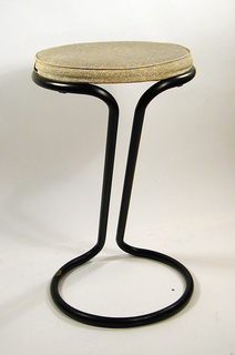Stool; upholstered round seat supported by black metal tubular frame shaped into circle around seat leading to leg of two continuing tube and finally to a second circular frame on floor.