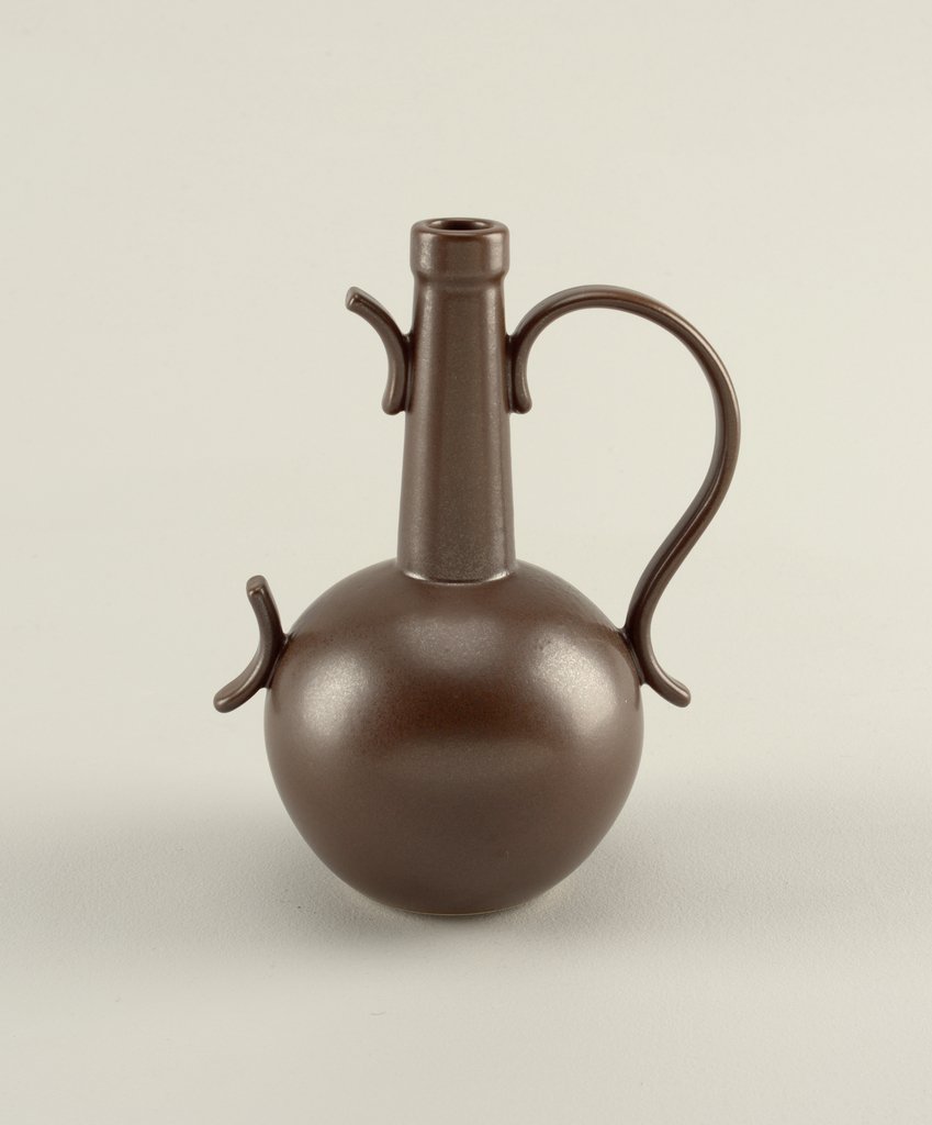 """Matte dark brown vase: globular body with tall, tapering cylindrical neck and circular mouth; large, S-curve loop handle on one side, short curving projections on opposite side, suggesting """"missing"""" loop handle."""
