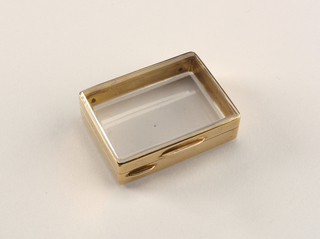 Rectangular, snuff-box type container with transparent glass top and bottom and gold sides. Glass beveled at edges, two gold thumb catches on front side of container. Lid hinged at back. Striker below hinge on back.