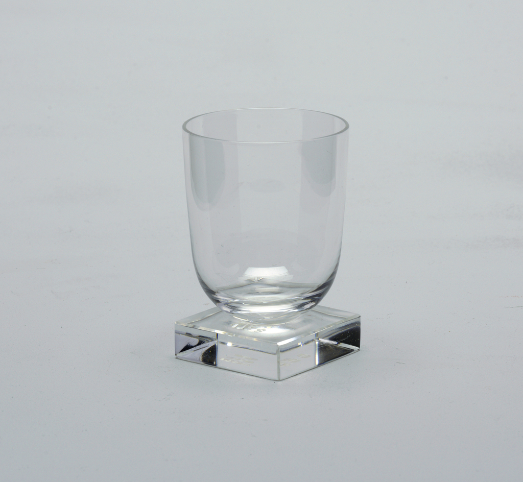 Clear glass with rounded base on a solid glass square foot.