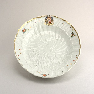 Molded with two swans swimming in rough water among fish and shells and flanked by bulrushes, a heron wading with a fish in its beak another in flight above, on a spiral shell-mounted ground. Decorated with a gilt rim and a large coat-of-armor at the top beneath border.