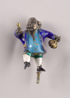 Enameled and gilt metal figurine of bald-pated man holding brass decanter and wine glass. Enameled costume: royal blue jacket with tan belt, blue waistcoat with red buttons, green breeches, white stockings, black shoes. Threaded pin for support on base of left foot.