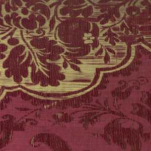 Red furnishing fabric with a large-scale symmetrical floral pattern in red with a yellow border of flowers, lattice and shell-like motifs.