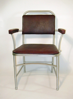 Thin rounded frame chair made in aluminum with armrests. Burgundy leatherette upholstery is on the seat, upper back and armrests.