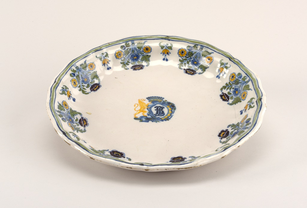 "Circular form with shaped rim; white ground with blue-green-blue bands on rim with sunflower lambrequins. Centered by rampant lion supporter of crown and rococo cartouche with monogram ""LB"" or ""BL""."