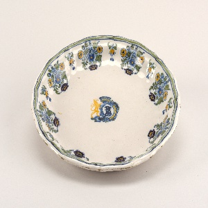 """Circular form with shaped rim; white ground with blue-green-blue bands on rim with sunflower lambrequins. Centered by rampant lion supporter of crown and rococo cartouche with monogram """"LB"""" or """"BL""""."""
