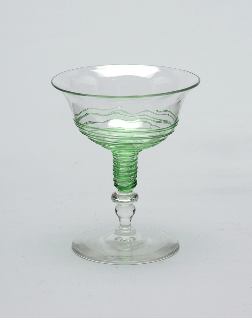 Clear glass, circular base, short baluster-shaped stem, shallow bowl flaresout towards rim. Light green threading applied to outside of lower section of bowl. Champagne saucer