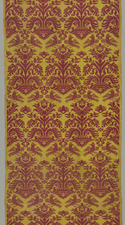 Brilliant yellow ground woven in cherry red with symmetrical design of alternating rows of upstanding floral shrubs surmounted by pairs of opposed birds. Wide yellow cloth selvedges. Lined; striped silk fringe.