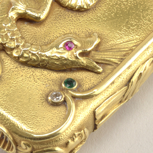 Rectangular, with rounded corners, featuring raised decoration of winged dragon with long, serpent-like tail that curls and extends up onto lid. Dragon has single red ruby for eye. Creature is framed on right and left by raised vertical bands; their ends curve inward and terminate with emeralds at each point. Above right and left, on lid, and below on lower section of box, are short, raised, curved bands that terminate at a single point with diamonds, each point abutting one of the four emeralds. The same decorative raised bands, two long, four short, are repeated on the reverse, with four rubies, instead of emeralds, framing incised monogram, and diamonds above and below. Featured, from top to bottom on each vertical side is a dolphin, a cloth-draped winged female or harpy in profile, and a head in profile, terminating in three decorative scrolls, the stems of which abut the lozenge shaped, grooved and recessed striker on bottom. Parts of undecorated surfaces slightly stippled. Lid hinged on side. Link attached to back of lid.