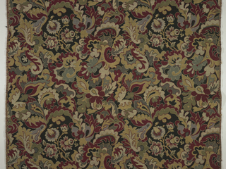 Length of upholstery fabric with elaborate leaf forms of red, gold, green and grey frame branch of flowers of same color. Woven imitation of wool needlepoint. Black background.