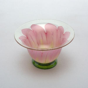 Clear glass bowl with flared rim showing ten pink petals with green at base, green foot.