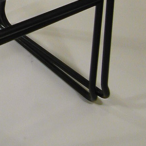 Stacking chair with frame formed by black metal tubes as side stretchers and stretcher at front; canvas seat and back.