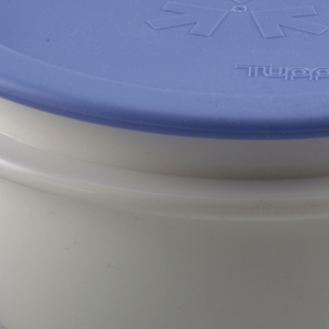 Bowl is white with small handles on opposite sides, and lid is light blue with Tupperware logo.