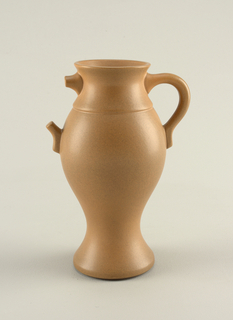 "Matte tan glazed amphora form, the globular body with flaring circular mouth, circular foot; loop handle on one side, two projections on opposite side appearing as top and bottom of ""missing"" handle."