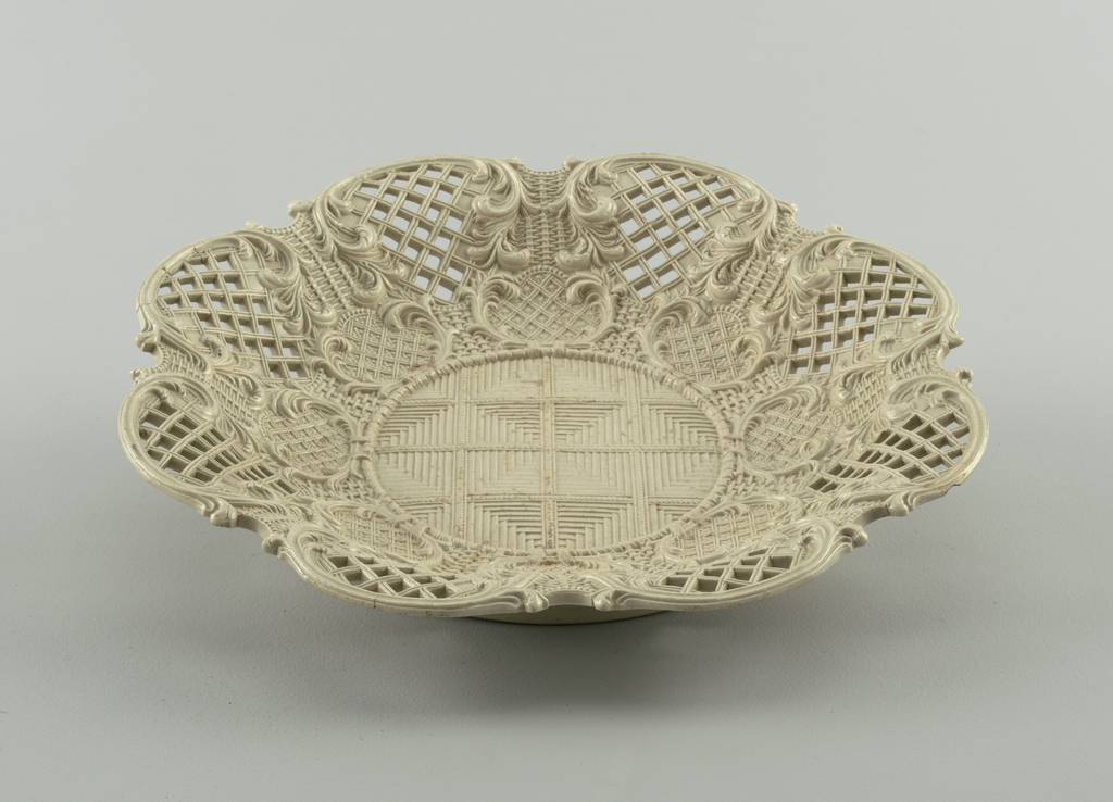 Round, low basket, molded to resemble weaving. Scrollwork and piercing along sides.