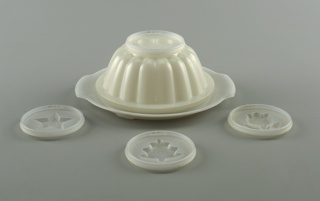 Lobed circular mold/bowl of white plastic; circular tray; 4 circular mold lids, each with a raised decoration: star, flower, heart, Christmas tree.