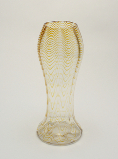 Tall baluster form vase of clear glass with wavy amber-colored horizontal threads in body.