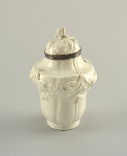 Inverted acorn shaped with cavetto neck and domed cover with floral knob. Cylindrical foot; side broken by four vertical grooves alternating with four ridges. Floral festoons in relief on shoulders, flowers in relief upon covers, which have silver rims.