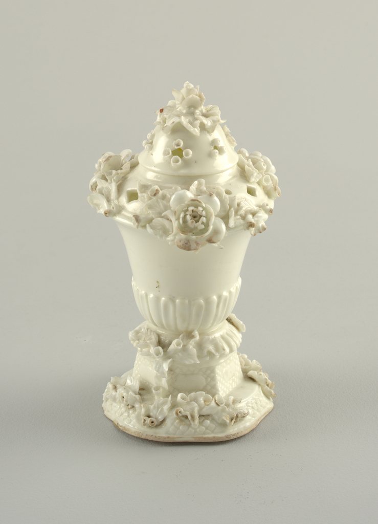"""In the form of a vase with vertical gadrooning. Modelled flowers on the pierced dome lid and octagonal base. Unpainted """"blanc de chine"""" surface. Ceramic body without glaze visible at base."""